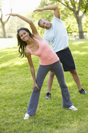 couple exercising: Young African American Couple Exercising In Park Stock Photo