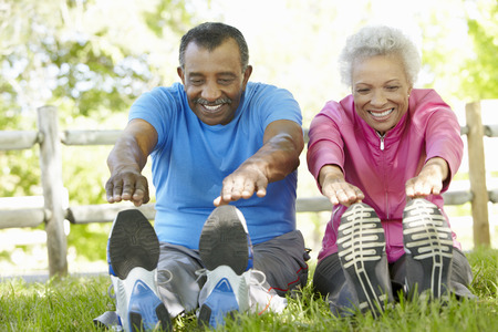 Senior African American Couple Exercising In Park