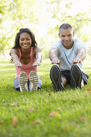 african american woman smiling: Young African American Couple Exercising In Park Stock Photo