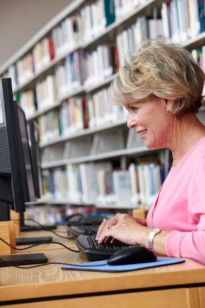 persona de la tercera edad: Mujer mayor que trabaja en la computadora en la biblioteca Foto de archivo
