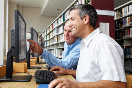 Men working on computers in library Stock Photo