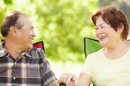 senior asian: Senior couple sitting outdoors