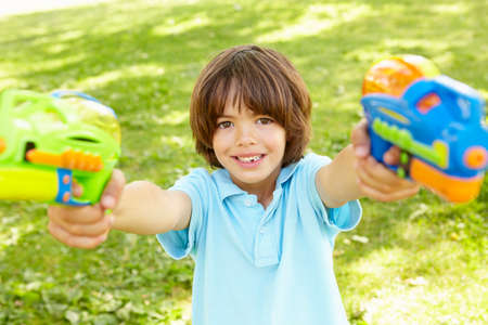 naughty boy: Young Boy Playing With Water Pistols In Park Stock Photo