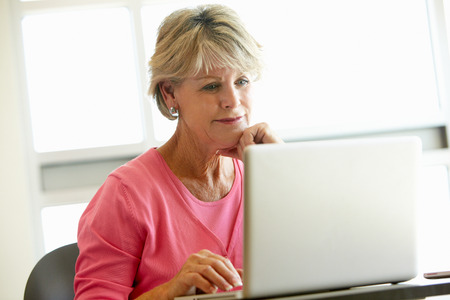 Mature student using computer in class Stockfoto