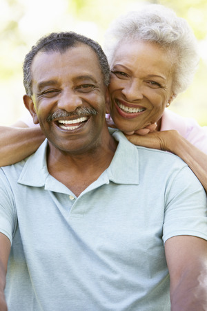 african american woman smiling: Portrait Of Romantic Senior African American Couple In Park
