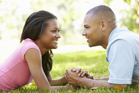 mixed race couple: Portrait Of Romantic Young African American Couple In Park