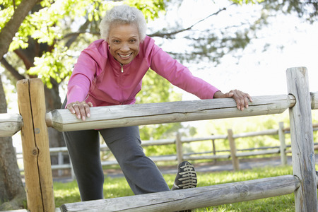 touching toes: Senior African American Woman Exercising In Park
