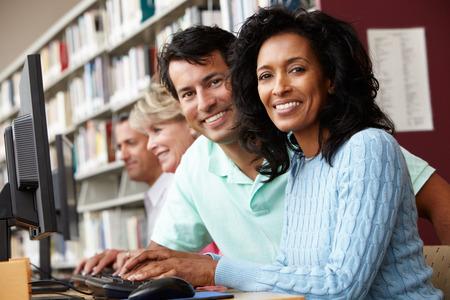 mujeres ancianas: Los estudiantes trabajan en los ordenadores en la biblioteca
