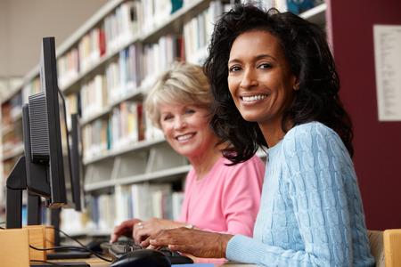 ライブラリ内のコンピューターで働く女性