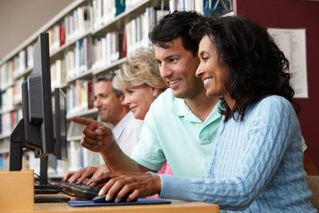 Studenten die op computers in bibliotheek werken Stockfoto