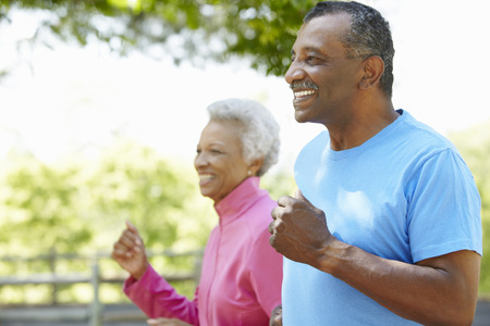 Senior African American Couple Jogging In Park. Stock Photo