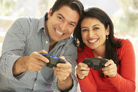 playing video game: Hispanic Couple Playing Video Game At Home