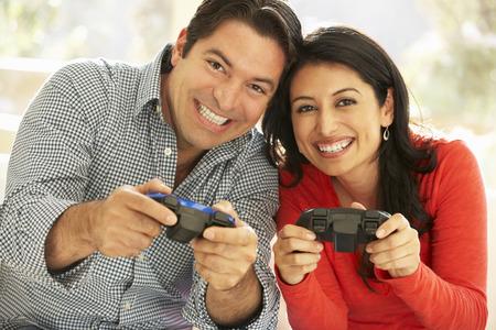 pareja en casa: Pares hispánicos que juegan videojuegos en casa