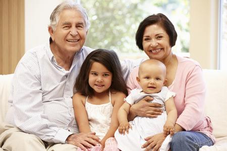 孫を持つヒスパニック祖父母家で 写真素材