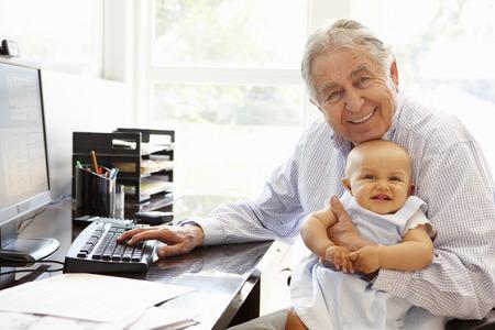 hombres maduros: Hombre hisp�nico mayor con el ordenador y el beb�