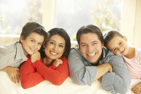 familias jovenes: Familia hispánica joven que se relaja en el sofá en casa Foto de archivo