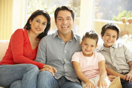 家族: 若いヒスパニック家族、自宅のソファーでリラックス