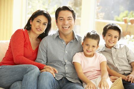 aile: Evde Sofa On rahatlatıcı Genç Hispanik Aile Stok Fotoğraf