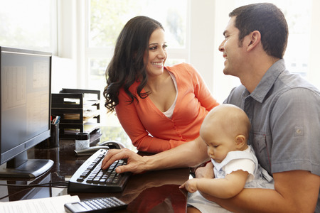working man: Hispanic couple and baby in home office