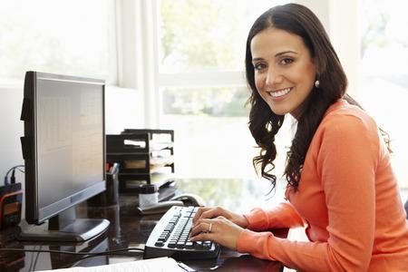 mecanografía: Mujer hispánica que trabaja en la oficina en casa