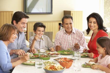 Familiares hispana disfruta de la comida en casa