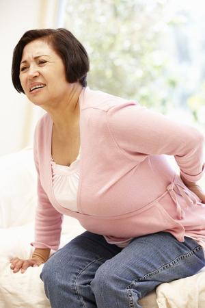 Hogere Spaanse vrouw met rugpijn Stockfoto