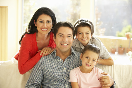Young Hispanic Family Relaxing On Sofa At Home Stock Photo