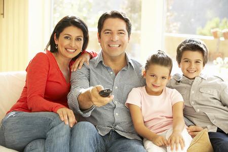 家庭: 年輕的西班牙裔家庭在家裡看電視 版權商用圖片