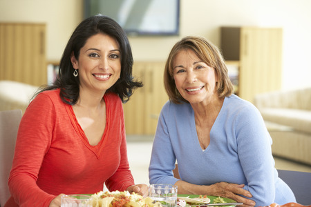30s adult: Hispanic Mother With Adult Daughter Enjoying Meal At Home