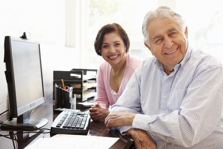 Senior Hispanic couple working on computer at home Stockfoto
