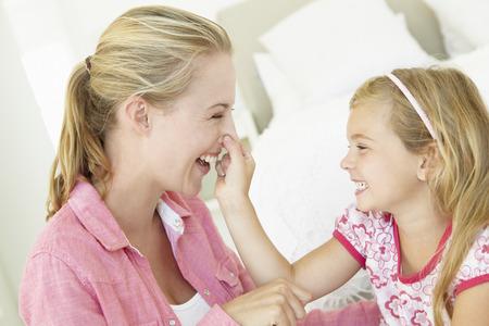 mother with daughter: Madre e hija jugando juntos en el dormitorio