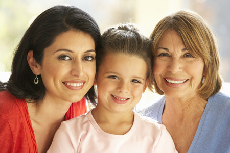 Portrait Of Hispanic Grandmother, Mother And Daughter Relaxing At Home Stock Photo