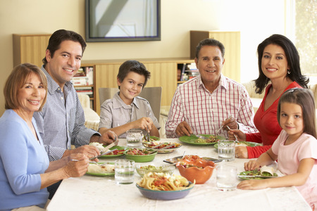 family with three children: Extended Hispanic Family Enjoying Meal At Home