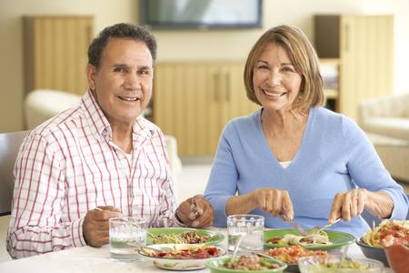 eating dinner: Senior Hispanic Couple Enjoying Meal At Home