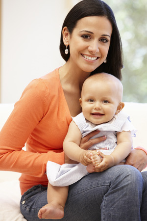 mom holding baby: Hispanic mother and baby at home Stock Photo