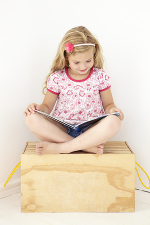 toy box: Young Girl Sitting On Wooden Toy Box Reading Book In Bedroom