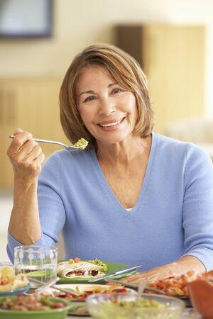 eating dinner: Senior Hispanic Woman Enjoying Meal At Home Stock Photo