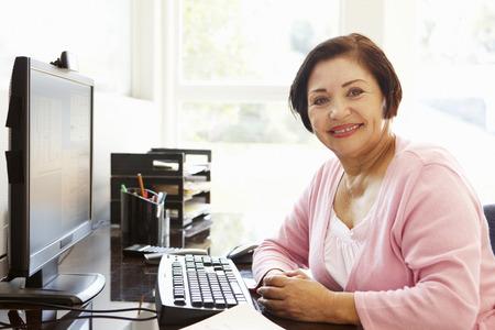 Hogere Spaanse vrouw die aan computer thuis werkt Stockfoto