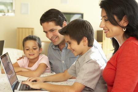 Jonge Spaanse Familie die computer thuis met