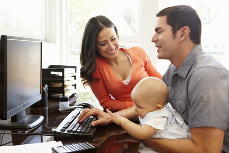Hispanic couple and baby in home office