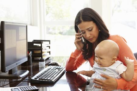 mujer hijos: Hispanic madre con el bebé que trabaja en la oficina en casa Foto de archivo