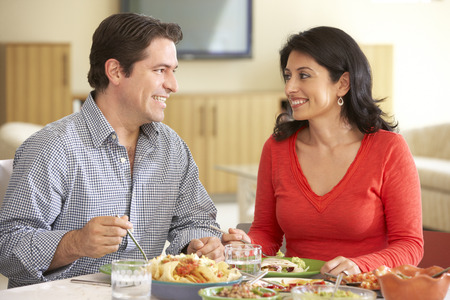 male age 40's: Young Hispanic Couple Enjoying Meal At Home Stock Photo