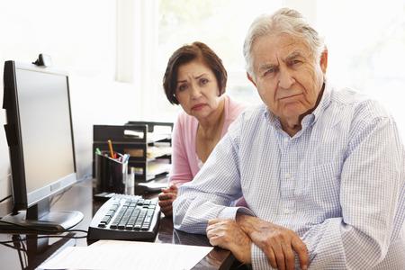 banking problems: Senior Hispanic couple working on computer at home Stock Photo