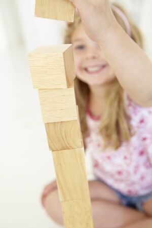 tower block: Young Girl Playing With Wooden Building Blocks In Bedroom