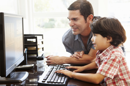 Hispanic father and son using computer at home 版權商用圖片