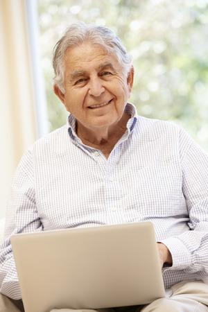 Senior Hispanic man with laptop Stock Photo