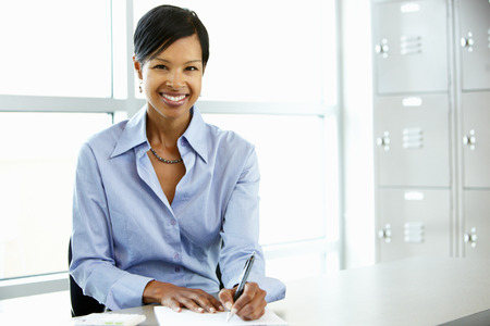 african american woman smiling: African American woman working at desk Stock Photo