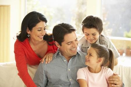 family indoors: Young Hispanic Family Relaxing On Sofa At Home Stock Photo