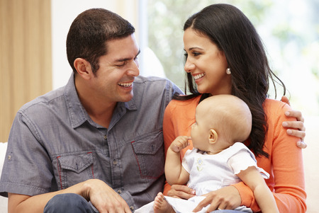 Hispanic couple at home with baby