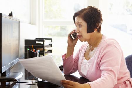 factura: Mujer hispana mayor que trabaja en el ordenador en el hogar